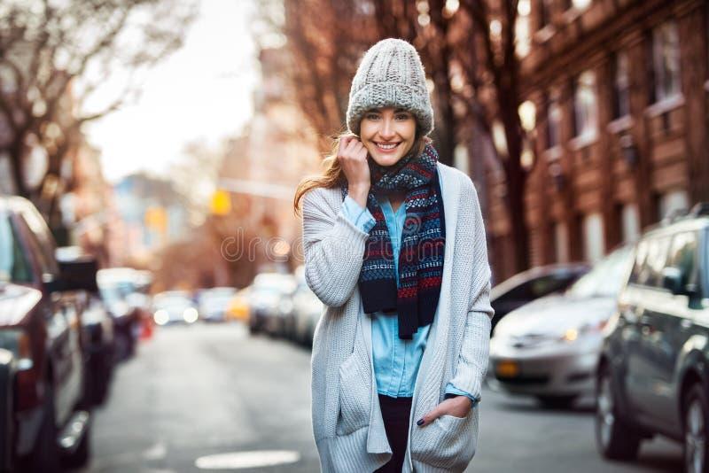 走在城市街道上的美丽的微笑的妇女佩带便装样式穿衣 图库摄影