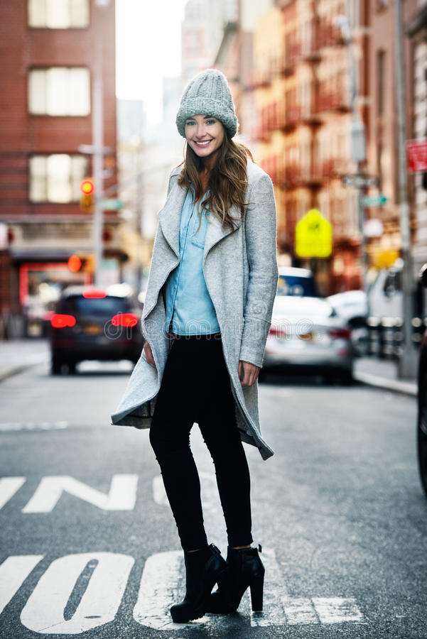走在城市街道上的美丽的微笑的妇女画象  图库摄影