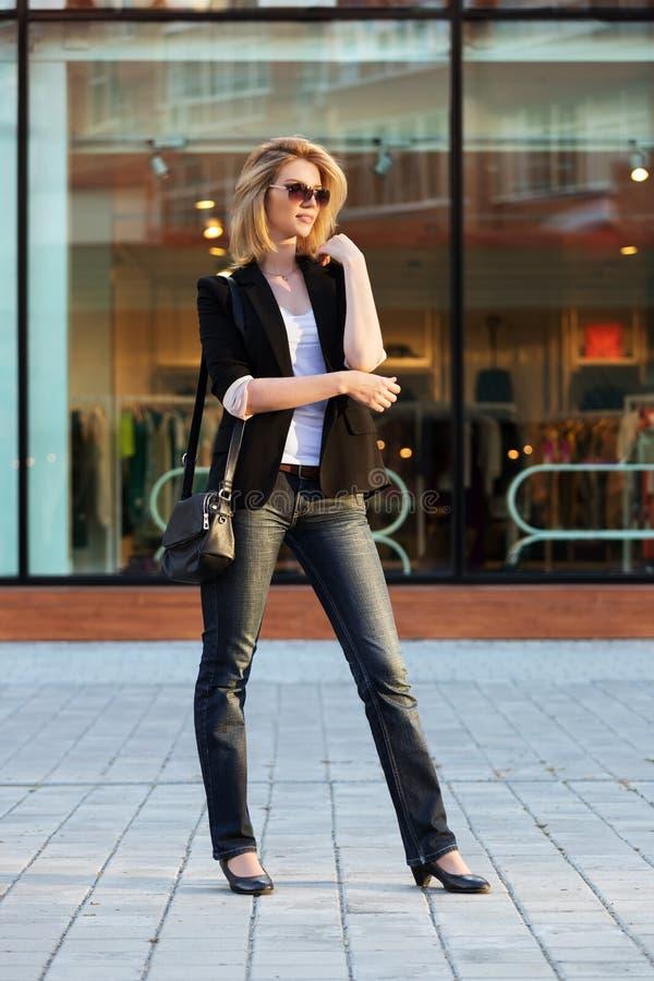 走在城市街道上的年轻时尚妇女 库存图片