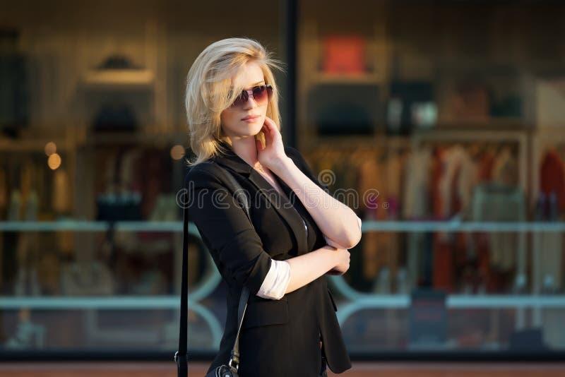走在城市街道上的年轻时尚妇女 免版税库存图片