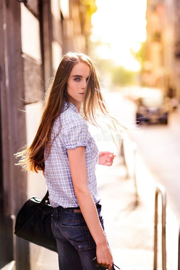 走在城市街道的美丽的妇女 免版税库存照片