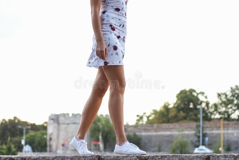 走在墙壁上的年轻可爱的白肤金发的女孩 图库摄影