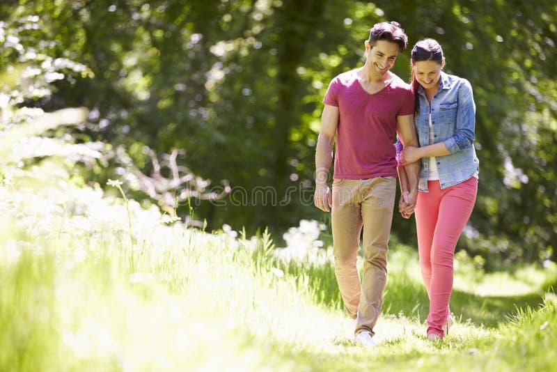 走在夏天乡下的年轻夫妇 库存图片