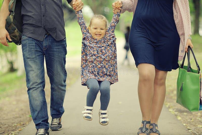 走在夏天的妈妈和年轻女儿和爸爸停放 免版税图库摄影