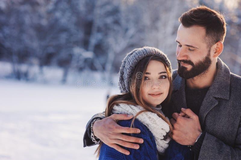 走在多雪的冬天森林里的愉快的爱恋的夫妇,花费圣诞节一起假期 室外季节性活动 免版税库存照片