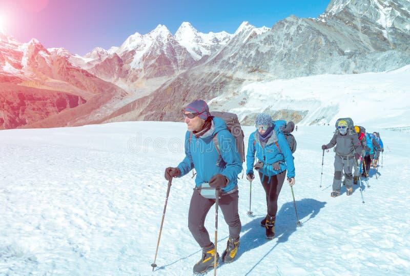 走在天气防护服装的冰川的爬山者 免版税库存照片