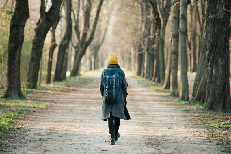 走在她的旅行旅途上的一条大道的年轻女人 免版税库存照片