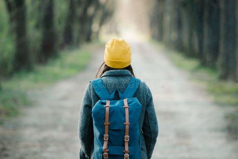 走在她的旅行旅途上的一条大道的年轻女人 免版税图库摄影