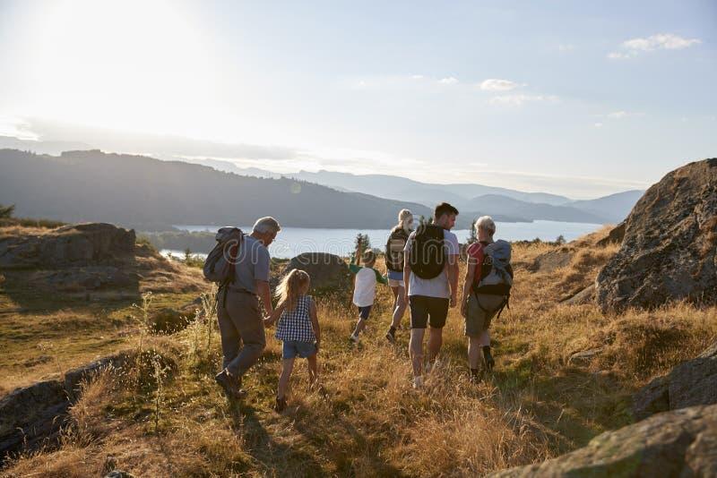 走在它上面在远足的小山的多一代家庭背面图通过乡下在湖区英国 免版税库存照片