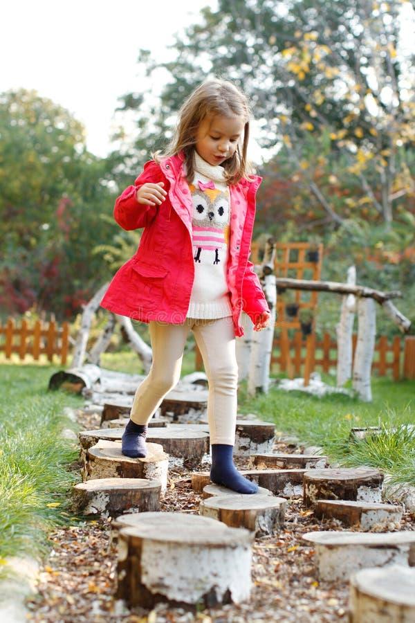 走在小卵石的四岁的女孩 免版税库存照片