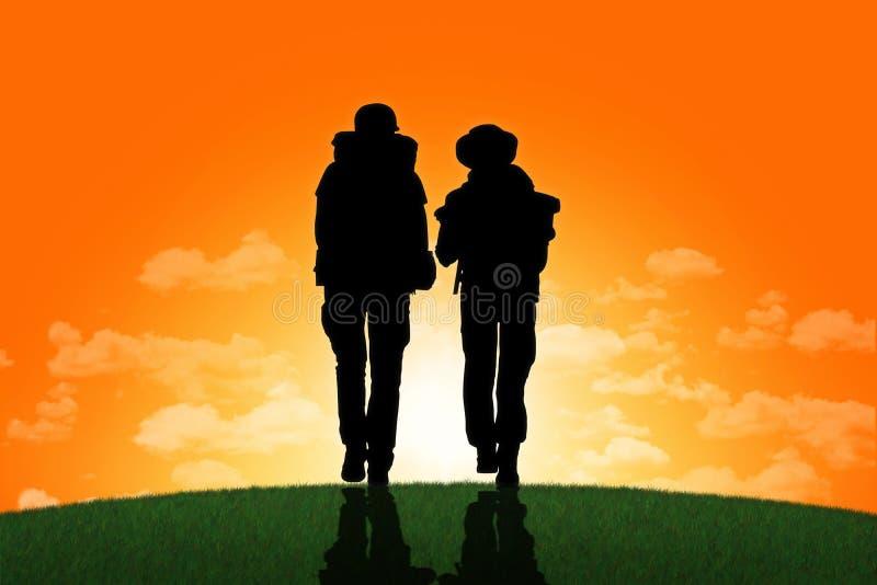 走在小山的上面的背包徒步旅行者夫妇在日落 皇族释放例证