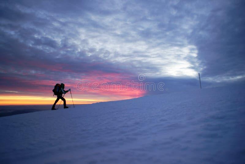 走在山的人由日落 库存图片