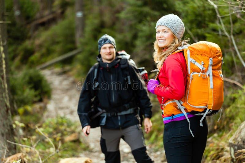 走在山的夫妇愉快的远足者 免版税图库摄影