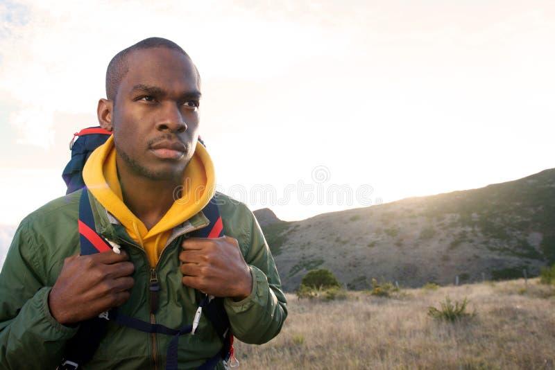 走在山的年轻黑人的关闭与背包清早 免版税库存图片