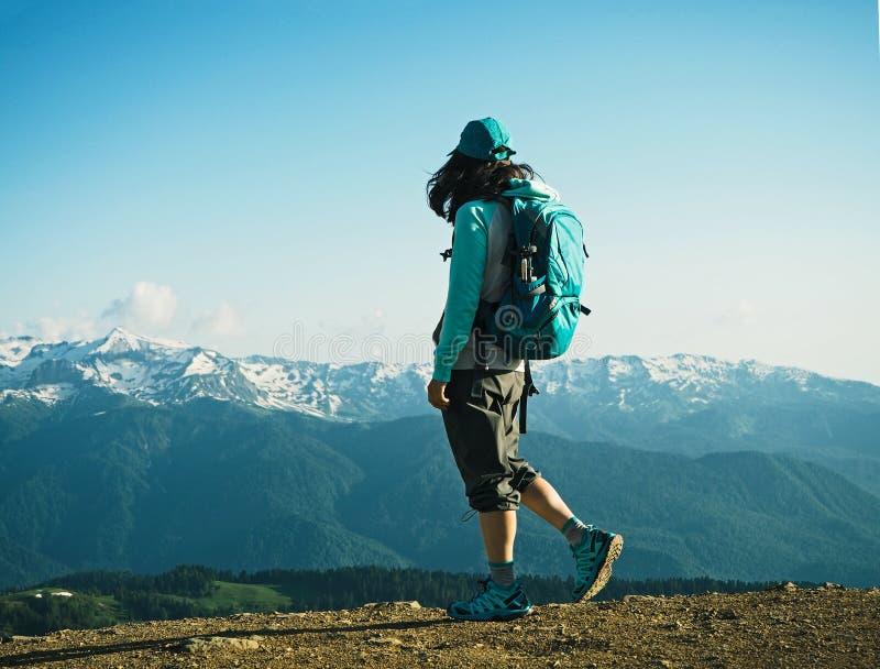 走在山背景的年轻活跃妇女 免版税库存照片