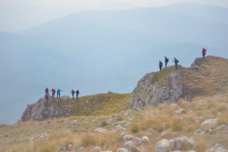 走在山行迹的人另外年龄和种族的在远足期间 免版税库存照片