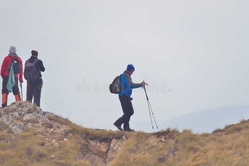 走在山行迹的人另外年龄和种族的在远足期间 免版税库存图片