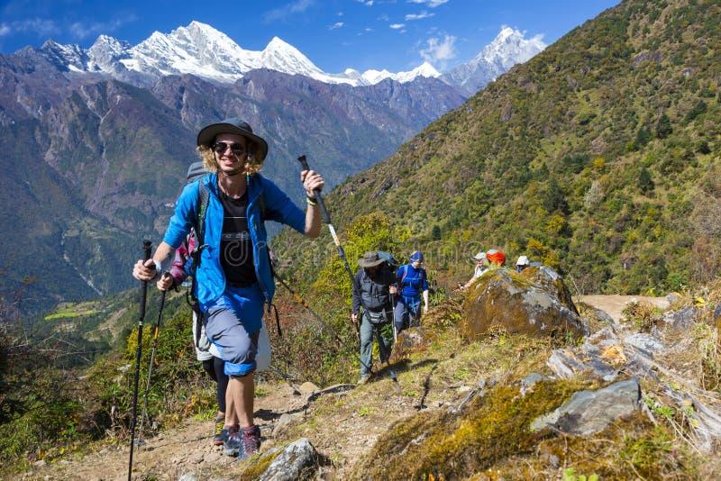 走在山行迹的激动的年轻人 免版税图库摄影
