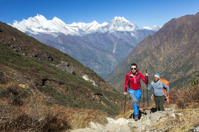 走在山行迹的年轻远足者与地方指南一起 库存照片