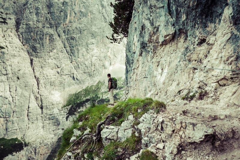 走在山行迹Cinque Torri,惊叹的年轻人背包徒步旅行者 库存照片