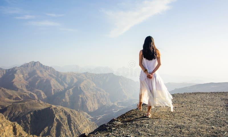 走在山边缘的女孩 免版税库存照片