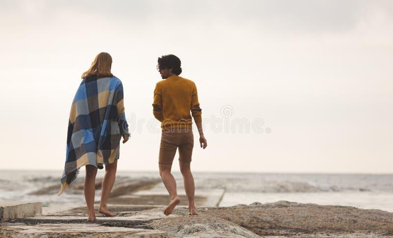 走在岩石的白种人夫妇在海滩附近 库存图片