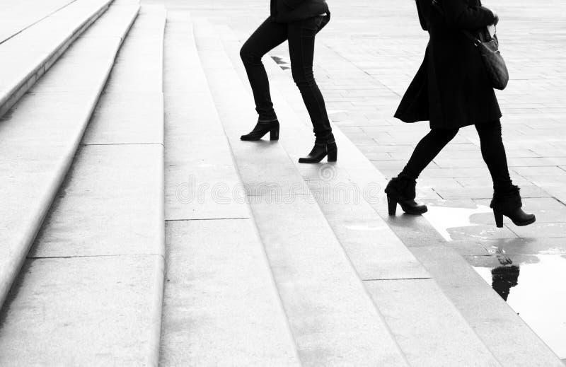 走在巨大城市台阶移动上下的两年轻女人 免版税库存图片