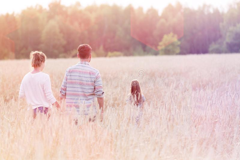 走在庄稼中的家庭背面图在农场 库存照片
