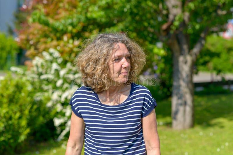 走在庭院里的可爱的中年妇女 免版税库存照片