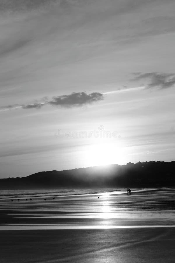 走在日出夏天天空的沙滩的人剪影在黑白 免版税库存照片