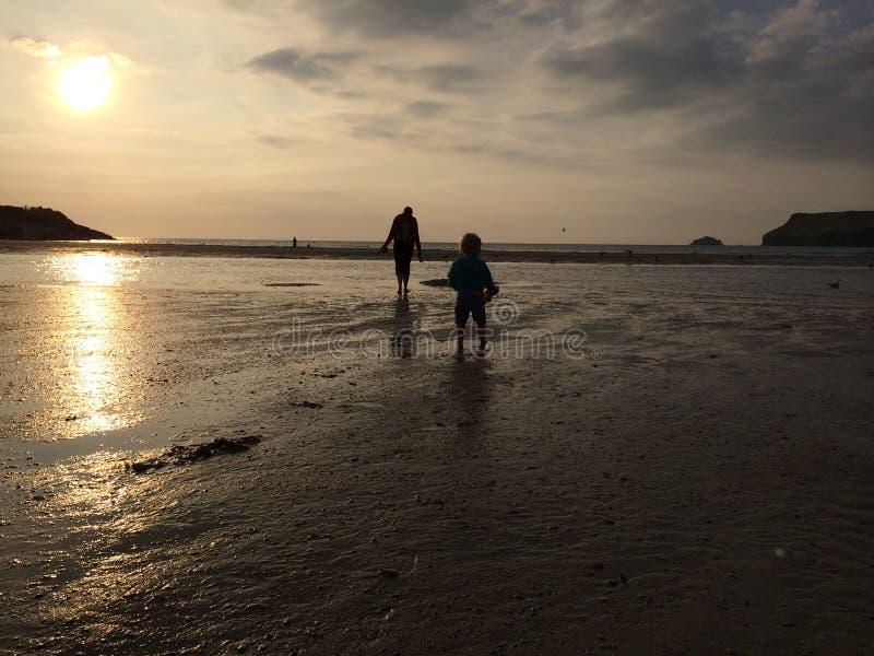 走在日落海滩的女孩和母亲 免版税库存照片