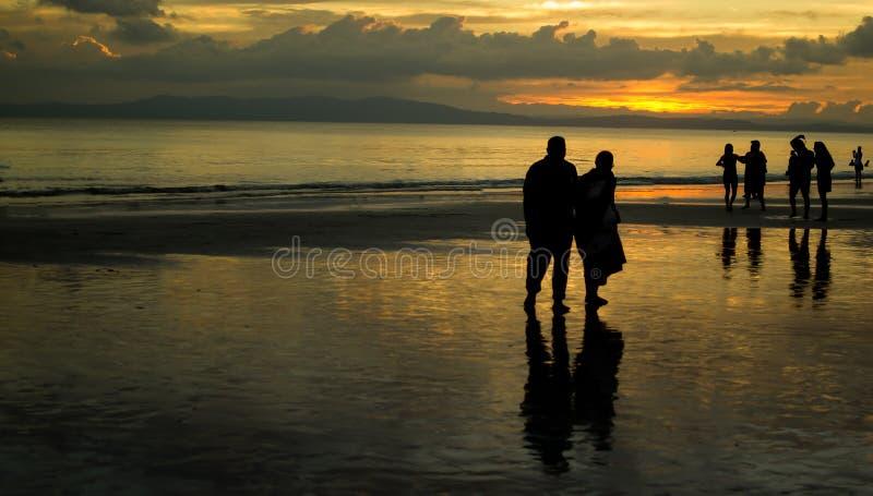 走在日落的一个海滩的年长夫妇 库存图片