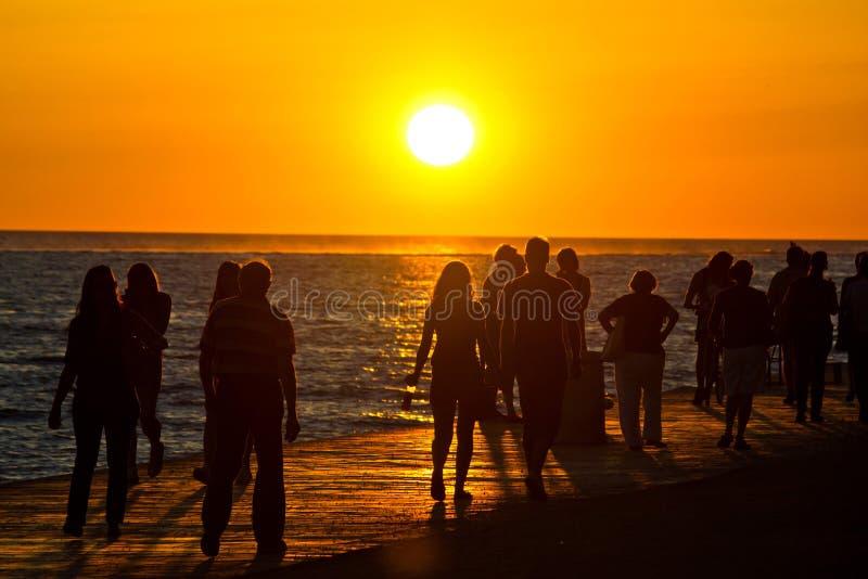 走在日落的江边的人们 免版税图库摄影