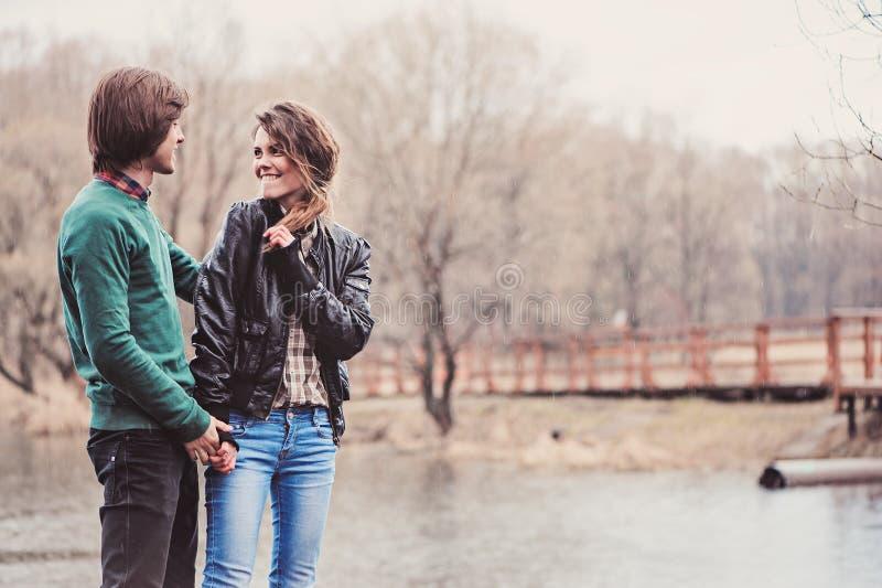 走在早期的春天的年轻愉快的爱恋的夫妇室外画象  免版税库存照片