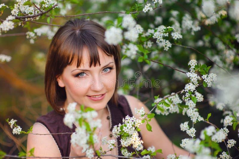 走在春天开花的庭院的美丽的女孩 库存照片