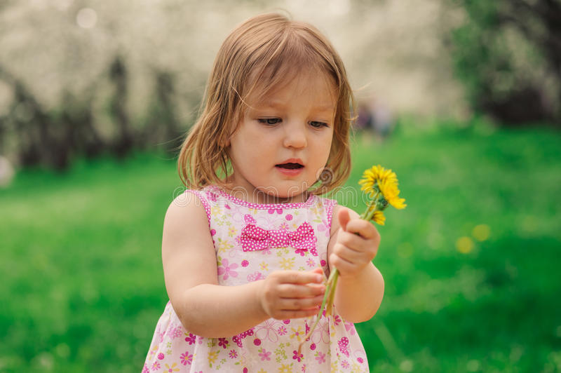 走在春天或夏天公园的逗人喜爱的矮小的愉快的小孩女孩画象 图库摄影