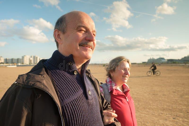 走在春天的海滩的资深夫妇 免版税库存照片