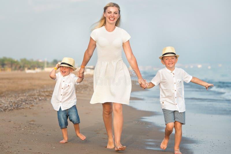 走在晚上海滩的家庭在日落期间 母亲儿子二 免版税库存照片