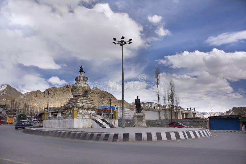 走在有交通的什卡拉路旁边的人们靠近Kalachakra Stupa环形交通枢纽在莱赫拉达克村庄在查谟-克什米尔邦,印度 库存照片