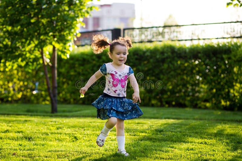 走在有她的母亲的草坪的滑稽的女孩 姐妹与妈妈一起使用 孕产照顾 E 免版税库存照片