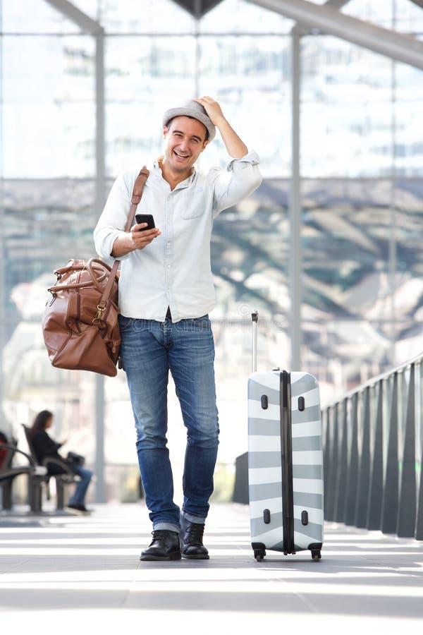 走在有手提箱袋子和手机的机场终端的愉快的旅行人 库存照片