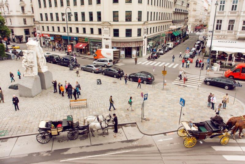走在有汽车和历史大厦的城市广场的游人和其他人民Croud  免版税库存照片