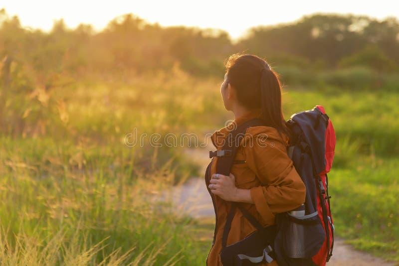 走在有背包的国家公园的远足者亚裔妇女 妇女游人去的野营在草甸森林里, 免版税库存图片