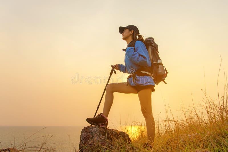 走在有背包的国家公园的远足者亚裔妇女 妇女游人去的野营在草甸森林,日落背景里 图库摄影