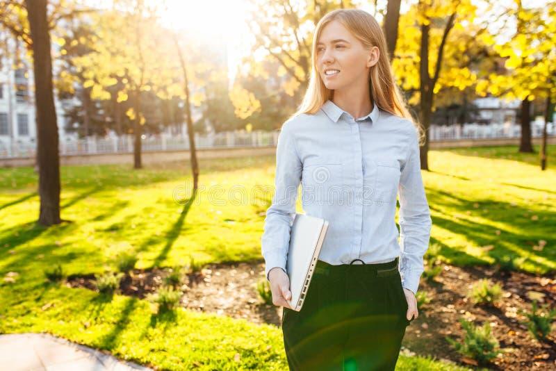 走在有膝上型计算机的公园的企业美女在日落 库存图片