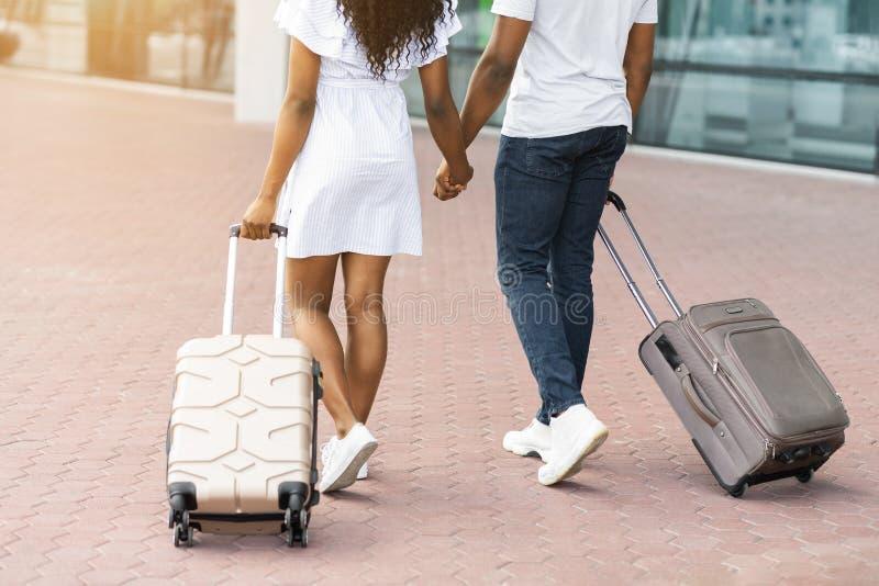 走在有行李的机场的年轻非洲家庭 库存图片