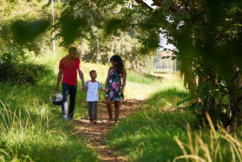 走在有野餐篮子的城市公园的愉快的黑家庭 库存图片