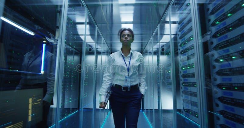 走在服务器机架中的妇女 免版税库存图片