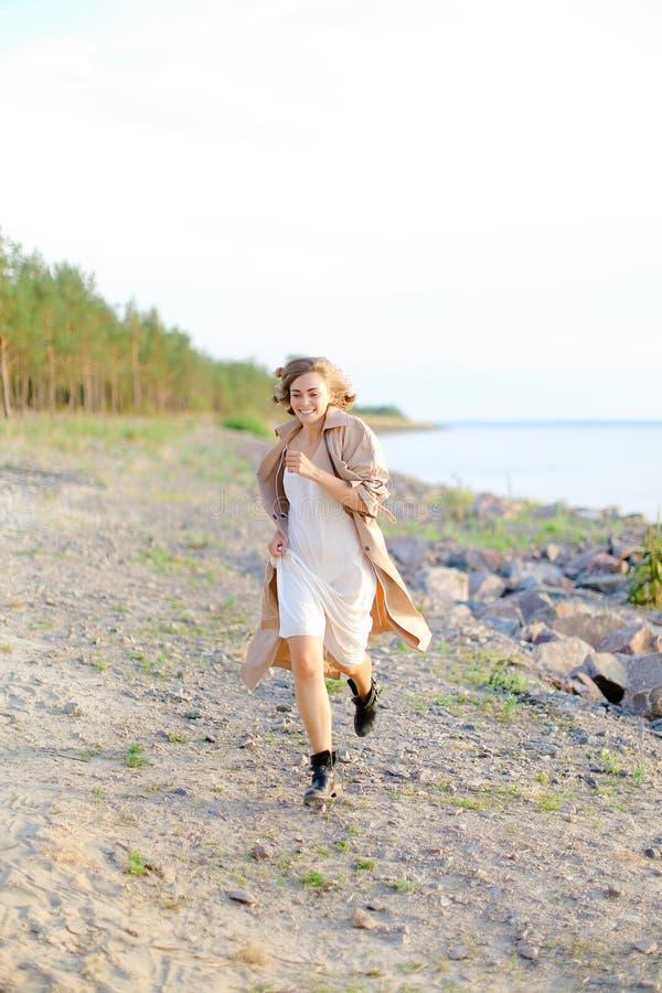 走在木瓦海滩和佩带的夏天外套的年轻俏丽的妇女 免版税库存图片