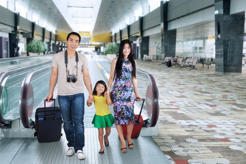 走在机场大厅里的家庭 免版税库存照片